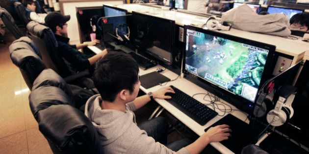 Shin Minchul, bottom, a 21-year-old college student, plays online computer games at an Internet cafe...