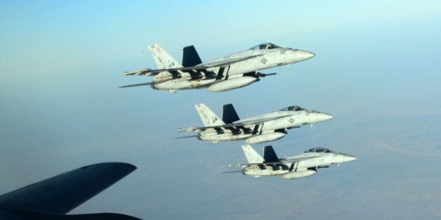 In this Tuesday, Sept. 23, 2014 photo released by the U.S. Air Force, a formation of U.S. Navy F-18E...