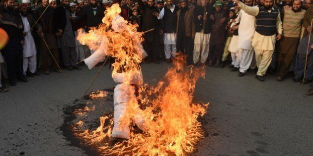 Pakistani protesters burn an effigy representing Charlie Hebdo cartoonists as they march against the...