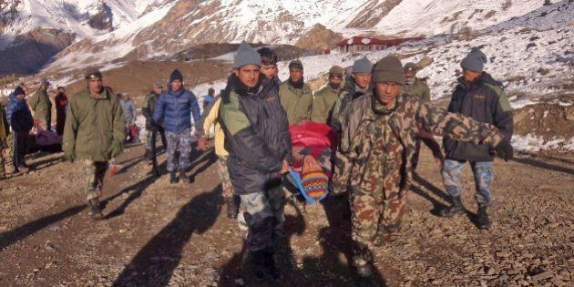 In this photo provided by the Nepalese army, soldiers carry an avalanche victim before he is airlifted in Thorong La pass area, Nepal, Wednesday, Oct. 15, 2014. An avalanche and blizzard in Nepal's mountainous north have killed at least 12 people, including eight foreign trekkers, officials said Wednesday. Five other climbers were hit by a separate avalanche on Mount Dhaulagiri and remain missing. (AP Photo/Nepalese Army)