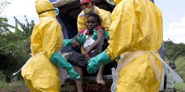 Health workers wearing protective suits assist a patient suspected of having Ebola on their way to an...