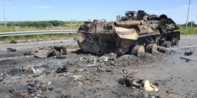 Photo taken on July 14, 2014 shows a destroyed armoured vehicle on the road of the airport in the south...