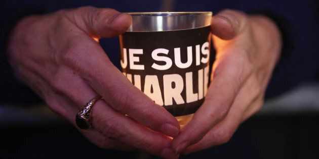 BERLIN, GERMANY - JANUARY 13: People hold candles with 'Je suis Charlie' written on them as they attend...