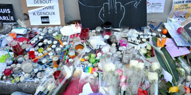 PARIS, FRANCE - JANUARY 14: Tributes of drawings, flowers, pens and candles are left near the Charlie...