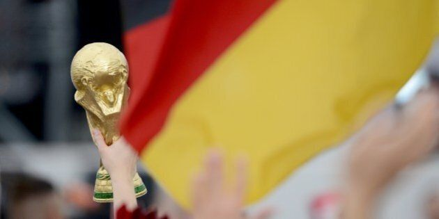 A person holds a fake trophy as German fans gather in front of a stage installed for a victory parade of Germany's football national team on July 15, 2014 at Berlin's landmark Brandenburg Gate to celebrate their FIFA World Cup title. Germany won their fourth World Cup title, after 1-0 win over Argentina on July 13, 2014 in Rio de Janeiro in the FIFA World Cup Brazil final game. AFP PHOTO / ROBERT MICHAEL        (Photo credit should read ROBERT MICHAEL/AFP/Getty Images)
