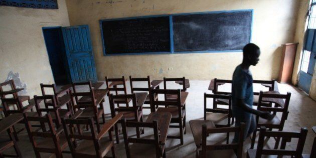 A boy walks on July 31, 2014 through an empty class room in a school in Monrovia which has been closed...