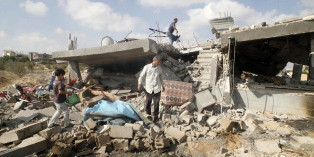 Palestinians salvage their belongings from their destroyed home in Rafah, in the southern Gaza Strip,...