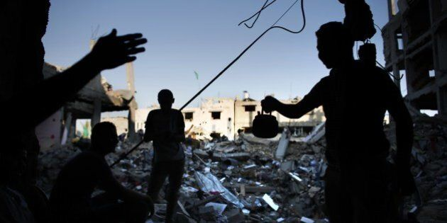 Palestinians have tea amidst the rubble of a destroyed house in Gaza City's Shejaiya neighbourhood on...