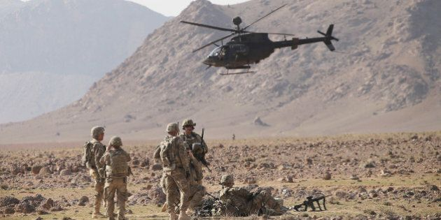 KANDAHAR, AFGHANISTAN - MARCH 06: A Kiowa Warrior helicopter flies above soldiers with 4th Squadron 2d...