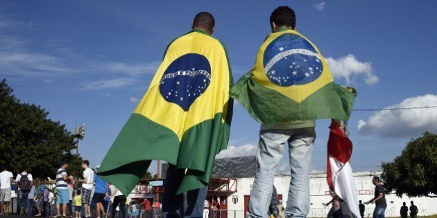 People wearing Brazilian flags arrive at the Santa Cruz Stadium in Ribeirao Prato to attend a France's national football team training session on June 10, 2014, a few days prior to the start of the 2014 FIFA World Cup in Brazil. AFP PHOTO / FRANCK FIFE (Photo credit should read FRANCK FIFE/AFP/Getty Images)
