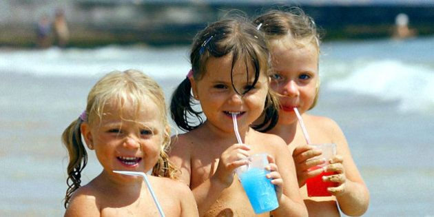 (Left to right): Finn family sisters Maisie, 2, and twins Mollie and Millie, 3, from Bournemouth, cool down with iced drinks at Bournemouth beach in Dorset, as weather forecasters predicted the hottest July day since 1911.
