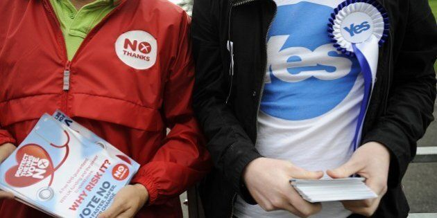 Pro-independence (R) and pro-union campaigners are pictured outside a polling station in east Glasgow,...