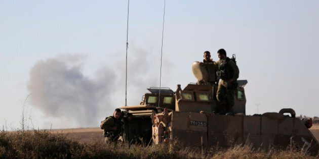 Israeli solders look on the site near the Israeli Gaza border, where a man was injured from a mortar...