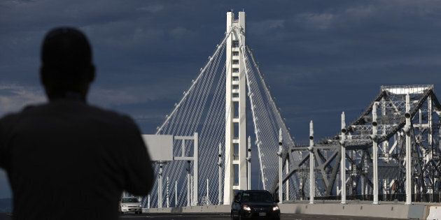 SAN FRANCISCO, CA - SEPTEMBER 02:  A California Highway Patrol officer looks on as a procession of cars crosses the new eastern span of the San Francisco Oakland Bay Bridge following a chain-cutting ceremony to mark the opening of the bridge on September 2, 2013 in San Francisco, California. After nearly 12 years of construction and an estimated price tag of $6.4 billion, the new eastern span of the Bay Bridge will open to traffic a day ahead of schedule. The bridge will be the world's tallest Self-Anchored Suspension (SAS) tower once completed.  (Photo by Justin Sullivan/Getty Images)