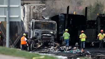 "Workers clear debris from the eastbound lanes of Interstate 70 on Friday, April 26, 2019, in Lakewood, Colo., after a deadly pileup involving semi-truck hauling lumber on Thursday. Lakewood police spokesman John Romero described it as a chain reaction of crashes and explosions from ruptured gas tanks. ""It was crash, crash, crash and explosion, explosion, explosion,"" he said. (AP Photo/David Zalubowski)"