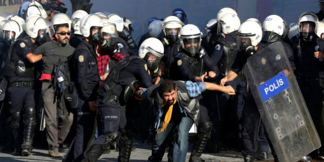 Turkish riot police detain protesters as they use tear gas to disperse people who were protesting against...