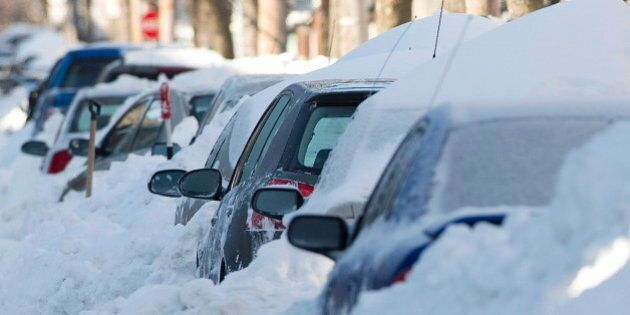 Cars are shown buried in snow in Montreal, Friday, Dec. 28, 2012, following the first major snowstorm...