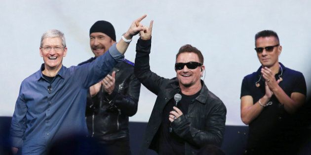 CUPERTINO, CA - SEPTEMBER 09: Apple CEO Tim Cook (L) greets the crowd with U2 singer Bono (2nd R) as...