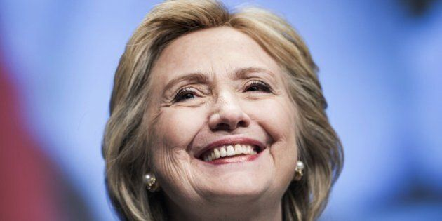 Former Secretary of State Hillary Clinton smiles before speaking at the World Bank May 14, 2014 in Washington,...