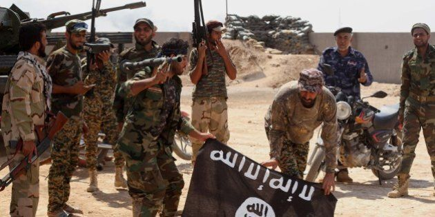 Iraqi security forces hold a flag of the Islamic State group they captured during an operation outside...