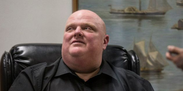 TORONTO, ON - NOVEMBER 21: Rob Ford sits in the reception area of his office to sign bobble heads. Lineups...