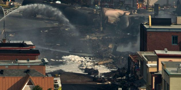 LAC-MEGANTIC QC - JULY 7: Firemen looked at the smouldering remains of a derailed train strewn among...
