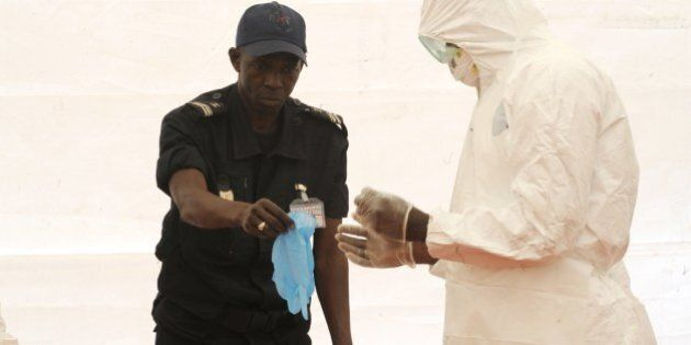 A Senegalese hygienist demonstrates how to protect oneself against the Ebola virus on April 8, 2014 at...