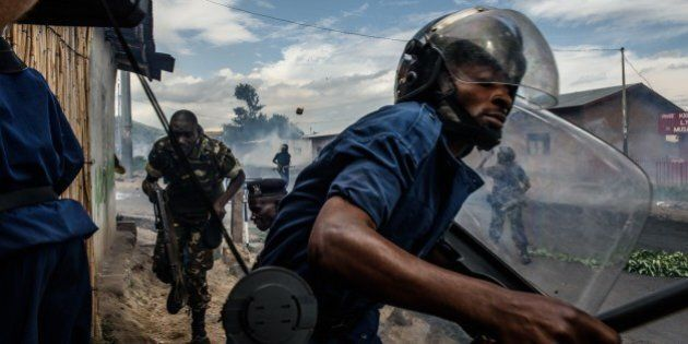 QUALITY REPEATA Burundian police officer holding a baton and army forces run after protestors throwing...