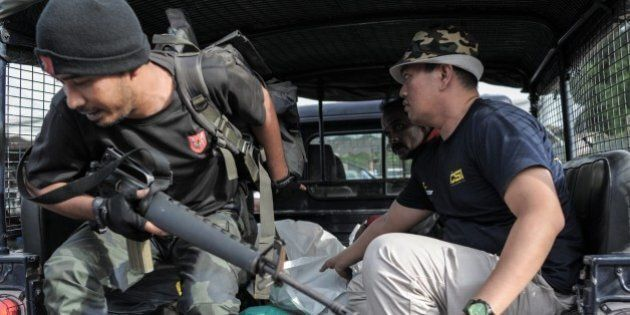 A Malaysian policeman dismounts from a truck transporting human skeletal remains inside plastic bags...