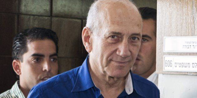 Former Israeli Prime Minister Ehud Olmert (C) leaves Tel Aviv's district court after a hearing in his...