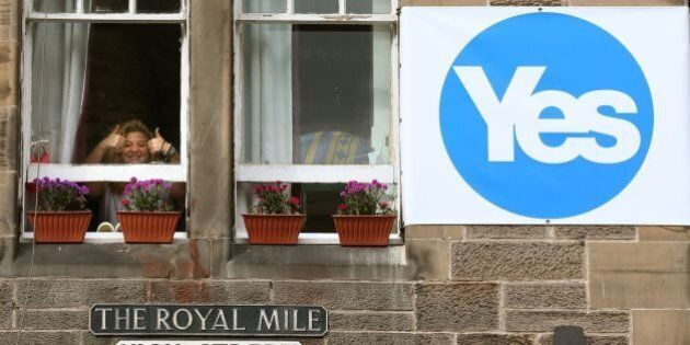 File photo dated 09/09/14 of a woman giving the thumbs up from a window in a property next to a YES sign...