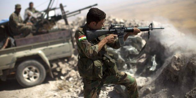 An Iraqi Kurdish Peshmerga fighter fires at Islamic-State (IS) militant positions, from his position...