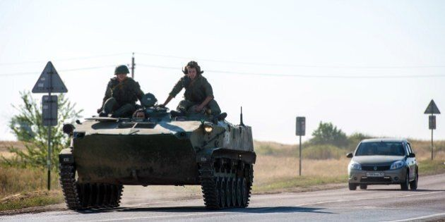 A Russian armoured personnel carrier drives on a road in the Russian-Ukrainian border area some 30 km...