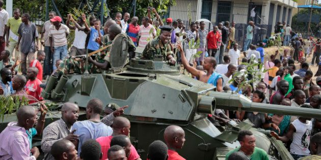 Demonstrators celebrate what they perceive to be an attempted military coup d'etat, with army soldiers...