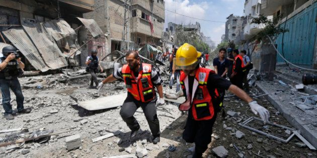 Palestinian medics carry a casualty as they run past a burning building in Gaza City's Shijaiyah neighborhood, northern Gaza Strip, Sunday, July 20, 2014. Dozens of people were killed in Shijaiyah and more bodies were believed buried under the rubble of homes, health officials said. (AP Photo/Lefteris Pitarakis)