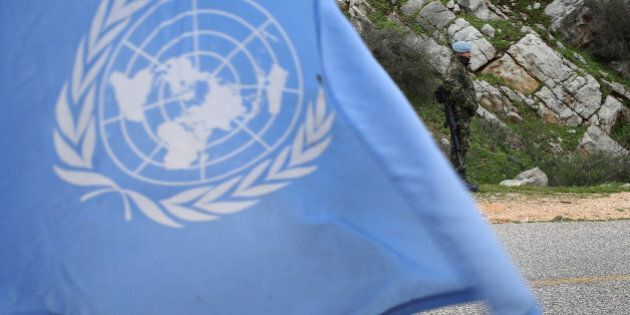 A United Nations flag waves as Spanish U.N. peacekeepers carry out a foot patrol in the disputed Chebaa...