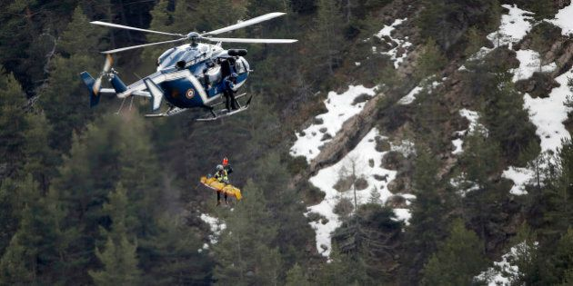 A rescue worker is lifted into an helicopter near the crash site near Seyne-les-Alpes, France, Thursday,...