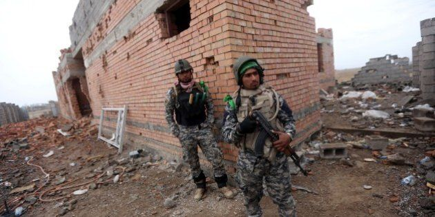Iraqi security forces stand next a damaged house in the southern entrance of the city of Tikrit on March...