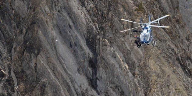 A helicopter carries investigators near scattered debris on the crash site of the Germanwings Airbus...