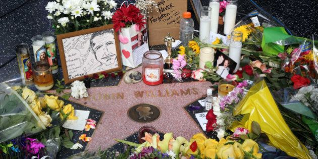 Flowers, photographs and candles surround the star of actor-comedian Robin Williams forming a makeshift...