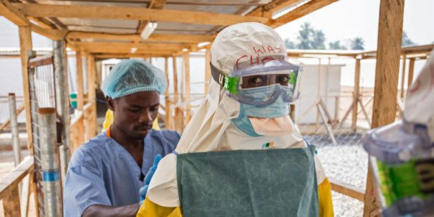 In this photo taken on Monday, March 2, 2015, a health care worker prepares a colleague's virus protective...