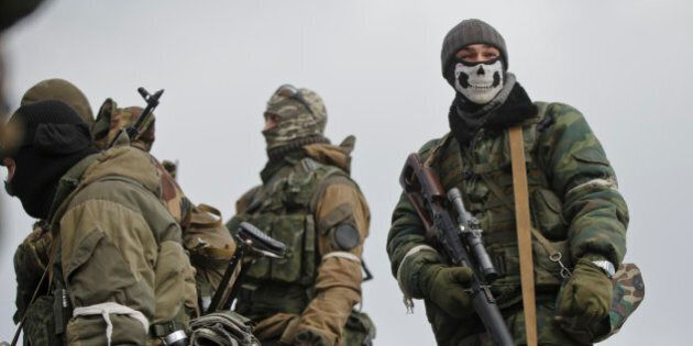 A Russia-backed rebel fighter holds a sniper rifle while a mask in Debaltseve, Ukraine, Friday, Feb....