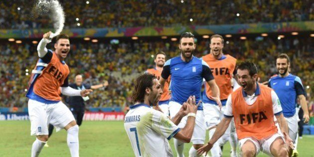 Greece's forward Georgios Samaras (C) celebrates with teammates after scoring a penalty during the Group...