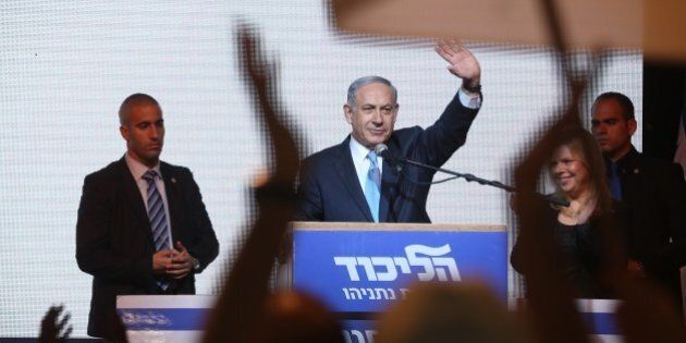 Israeli Prime Minister Benjamin Netanyahu (C) delivers a speech next to his wife Sara as he reacts to...