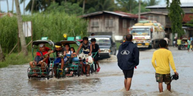 SULTAN KUDARAT, MINDANAO, PHILIPPINES - JULY 15: Residents cross a flooded road on July 15, 2014 in Sultan...