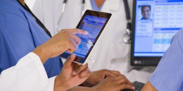 Doctors using digital tablet together in