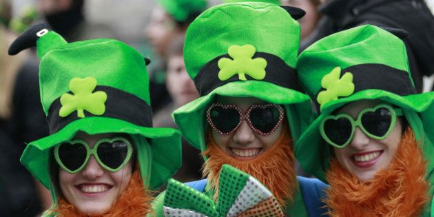 People dress in the emerald green to honour Ireland's Saint Partick, as they enjoy the atmosphere during the St Patrick's day parade in Dublin, Ireland, March, 17, 2014.  The world's largest parade celebrating Irish heritage set off on a cold and gray morning, the culmination of a weekend of St. Patrick's Day revelry. (AP Photo/Peter Morrison)