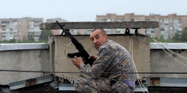 A pro-Russia militant shoots from a roof of a residential building at borderguards defending the Federal...