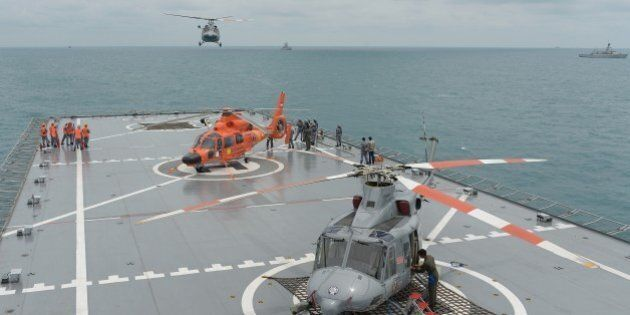 A navy helicopter arrives on the Indonesian navy vessel KRI Banda Aceh, close to area where search teams...