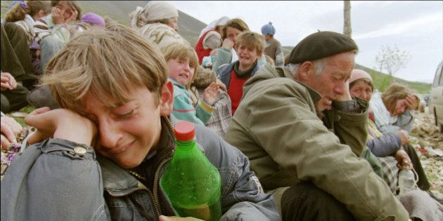 Kosovo Albanian refugees cry 15 April 1999 at the border between Yugoslavia and Albania near the northern...
